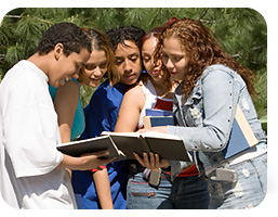 Students looking at a book outside